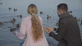 Back view of cheerful Caucasian couple feeding ducks on riverbank and chatting. Adult man and woman sitting on the shore