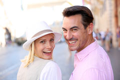 Back view of cheerful couple walking in street Stock Photo