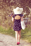 Back view of cheerful fashionable woman in stylish hat and frock Royalty Free Stock Photography