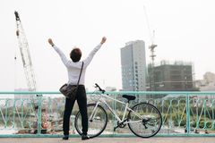 Back view of cheerful man with hands up with bicycle.  royalty free stock images
