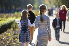 Back view of child girl and mother in dresses together holding hands on warm day outdoors on sunny background.  royalty free stock images