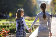 Back view of child girl and mother in dresses together holding hands on warm day outdoors on sunny background.  stock photography