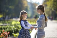 Back view of child girl and mother in dresses together holding hands on warm day outdoors on sunny background.  stock photos