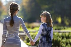 Back view of child girl and mother in dresses together holding hands on warm day outdoors on sunny background.  stock image