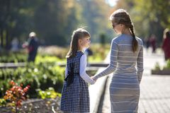 Back view of child girl and mother in dresses together holding hands on warm day outdoors on sunny background.  stock photo