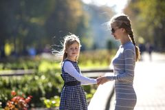 Back view of child girl and mother in dresses together holding hands on warm day outdoors on sunny background.  royalty free stock photography