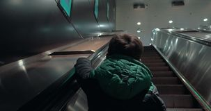 Boy moving up on escalator in subway. Back view of a child riding escalator and holding rails. He moving up and arriving at underground station hall stock video footage