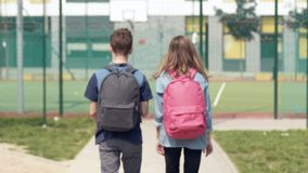 Back view children with bag. Back view - two schoolchildren go to school with backpacks. Cute children - teen girl and boy with bags Back to school. Concepts of stock video footage