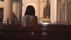 Back view of Christian woman praying in church. Back view of a young Christian woman sitting in the church while praying to the GOD. Shot in 4k resolution stock video
