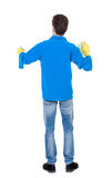Back view of a cleaner man in gloves with sponge and detergent. Stock Image