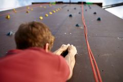 Back view close-up of climber hands on a rock hook of the artificial climbing wall outdoors. Young healthy sporty royalty free stock images