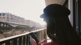 Back view close-up, happy beautiful creative worker woman using smartphone at idyllic sunny Paris balcony on vacation. stock footage