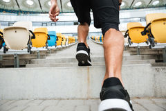 Back view close up of a male legs in sneakers running. On a staircase at the stadium Royalty Free Stock Photography