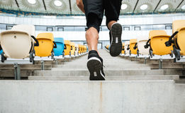 Back view close up of a male legs in sneakers running. Upstairs at the stadium Royalty Free Stock Photo