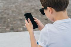 Back view. Close-up of smartphone in hands of boy. Teenager sits outdoor,uses gadget, browsing internet, checking email. stock photos