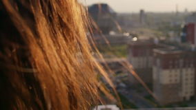 Back view. close-up Wind blows long dark hair beautiful young women. girl standing on the roof at sunset. Slow mo. Back view. close-up.Wind blows long dark hair stock footage