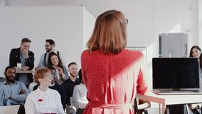 Back view coach business woman giving a talk at modern office seminar event for multiethnic team slow motion RED EPIC. stock video