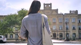 Back view of college student with long hair walking upstairs to university, ready to study.  stock video