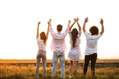 Back view. Company of young girls and guys are standing in the field on a summer day and holding their hands up.  stock image