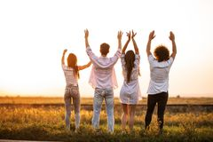 Back view. Company of young girls and guys are standing in the field on a summer day and holding their hands up.  stock photography