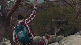 Back view of a complicated mountain path, and young people climbing down it. A young tourist grabs the branch of an old stock footage