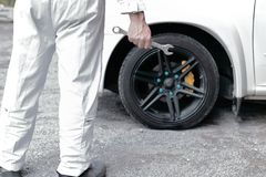 Back view of confident automotive mechanic in white uniform holding wrench in his hands ready to repairing car engine. Back view of confident automotive Stock Photography