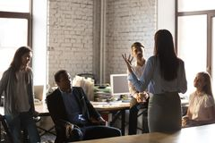 Confident female team leader hold casual meeting. Back view of confident businesswoman standing in front of colleagues, gesturing talking about business ideas or royalty free stock images