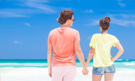 Back view of couple in bright clothes on tropical Stock Images