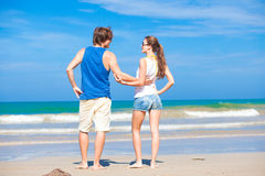 Back view of couple flirting on tropical beach in Stock Photography
