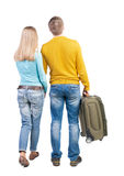 Back view of couple with  green suitcase looking up. Stock Photos