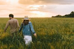 back view of couple holding hands and walking on green meadow royalty free stock photo
