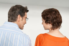 Back view of couple looking at each other against white wall Royalty Free Stock Image