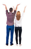 Back view couple  looking at wall and Holds  hand up. Stock Photography