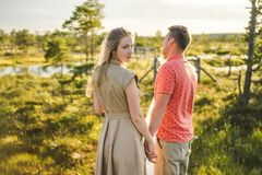 back view of couple in love holding hands on wooden bridge with green plants stock photography