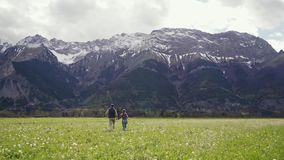Back view on couple in love running away holding hands on dandelion field with landscape snow mountains, spring. General. Plan 4k stock video