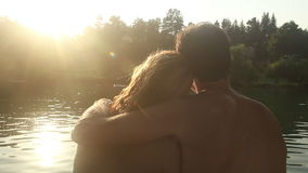Back view of couple in love sitting by the river at sunset stock video
