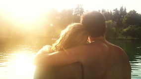 Back view of couple in love sitting by the river at sunset stock video footage