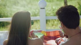 Back view of couple resting on the beach and clinking glasses with cocktails 4K.  stock footage