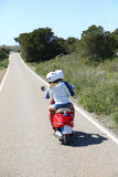 Back view of couple riding moto heading to the sea Royalty Free Stock Images
