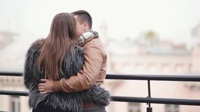 Back view of a couple on a roof of a building in a city. Lovers talk, laugh have great time together, enjoy the view. Of a city stock video