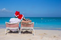 Back view of couple in Santa hats enjoy beach Royalty Free Stock Photo