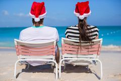 Back view of couple in Santa hats enjoy beach Stock Image