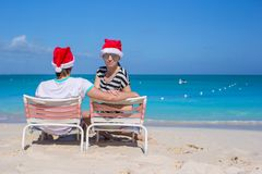 Back view of couple in Santa hats enjoy beach Royalty Free Stock Image