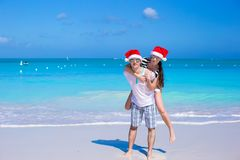 Back view of couple in Santa hats enjoy beach Royalty Free Stock Images