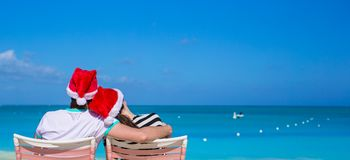 Back view of couple in Santa hats enjoy beach Stock Photography