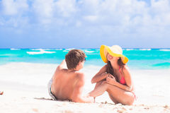 Back view of couple sitting on beach stock photos