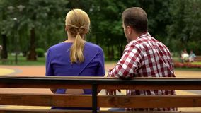 Back view of couple sitting on park bench, spending time together, conversation royalty free stock photography