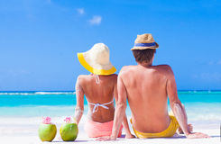 Back view of couple sitting on tropical beach with Stock Photography