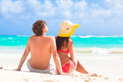Back view of couple sitting on a tropical beach in Stock Image