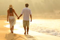 Back view of a couple walking on the beach at sunrise stock photography